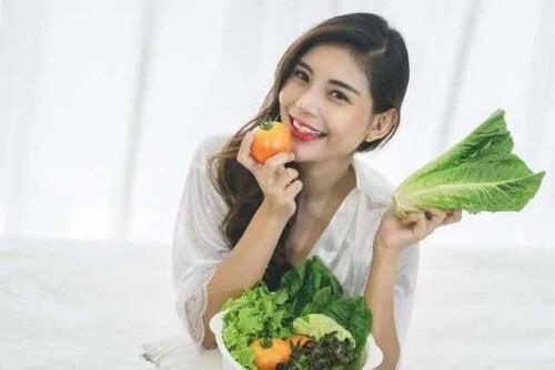 En kvinne som spiser ferske grønnsaker.