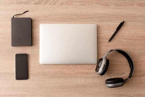 En planlegger, en smarttelefon, en bærbar datamaskin, en penn og hodetelefoner pent arrangert på et skrivebord.