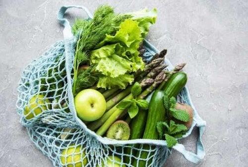En pose med grønt frukt og grønnsaker.