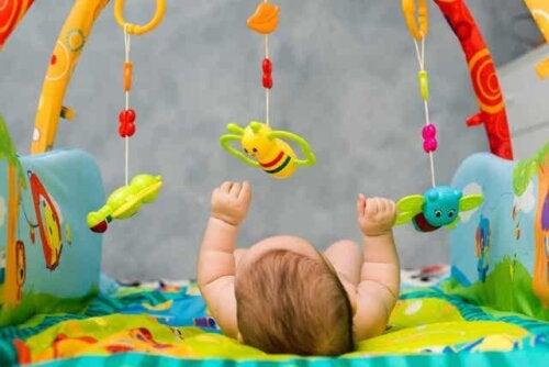 Et barn som ligger på ryggen og leker med et babygym.