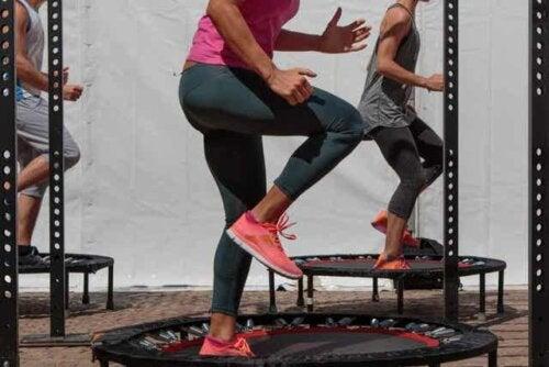 Flere voksne trener på individuelle trampoliner.