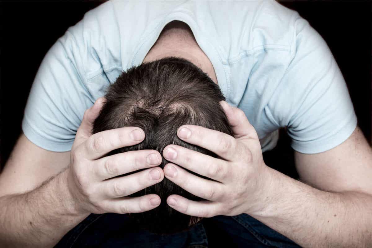 En mann holder hodet i hendene