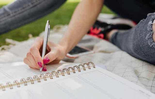 En kvinne som skriver i journalen sin.