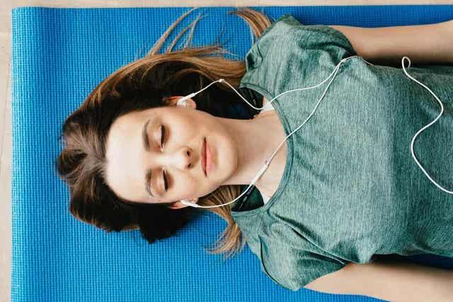 En kvinne som ligger på en matte med lukkede øyne og lyttet til hodetelefoner.