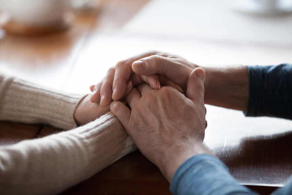 buli: to mennesker som holder hverandres hender støttende. F