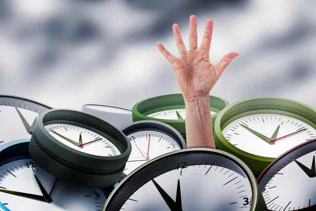 En hånd som strekker seg ut fra en haug med klokker