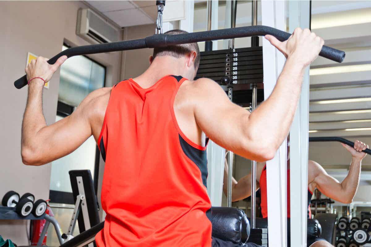 Typer stanggrep: en mann som bruker det tilbøyelige grepet på et treningsstudio.